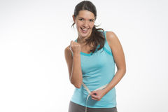 Happy fit young woman measuring her waistline. Caucasian happy fit young woman measuring her waistline after diet, on gray background royalty free stock photos