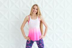 Happy young woman wearing sportswear smilig while posing near white wall Stock Image