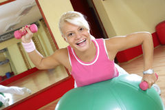 Happy fitness. Beautiful young woman on a big ball, lifting weights Stock Photos