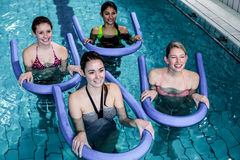 Happy fitness class doing aqua aerobics with foam rollers. In the pool Royalty Free Stock Photo