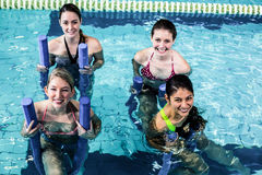 Happy fitness class doing aqua aerobics with foam rollers Stock Images
