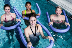 Happy fitness class doing aqua aerobics with foam rollers. In the pool Stock Photography