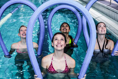 Happy fitness class doing aqua aerobics with foam rollers. In the pool Royalty Free Stock Images