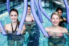 Happy fitness class doing aqua aerobics with foam rollers Stock Photography