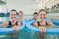 Happy fitness class doing aqua aerobics with foam rollers Royalty Free Stock Image