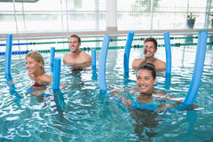 Happy fitness class doing aqua aerobics with foam rollers Stock Photos