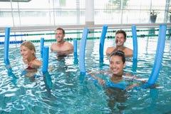 Happy fitness class doing aqua aerobics with foam rollers Stock Photos