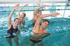 Happy fitness class doing aqua aerobics. In swimming pool at the leisure centre Royalty Free Stock Photo