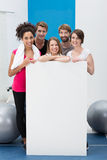 Happy fitness enthusiasts with a blank card Royalty Free Stock Photos