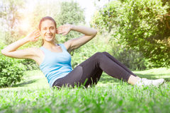 Happy fitness girl doing exercise Stock Photos