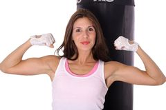 Happy Fitness girl flexing in front of punching ba Stock Image