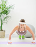 Happy fitness girl making push up exercise. On mat in gym stock photos