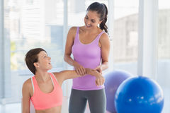 Happy fitness instructor with woman. Happy fitness instructor with women in exercise room Royalty Free Stock Photos