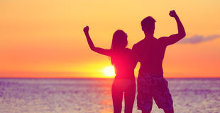 Happy Fitness People On Beach At Sunset Flexing Stock Photos