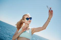 Happy fitness selfie blonde asian girl smiling and taking selfe. Happy fitness selfie blonde asian girl smiling and taking self portrait photograph with smart Royalty Free Stock Photography