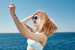 Happy fitness selfie blonde asian girl smiling and taking selfe. Happy fitness selfie blonde asian girl smiling and taking self portrait photograph with smart Stock Photography
