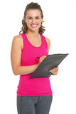 Happy fitness trainer writing something in clipboard Royalty Free Stock Images
