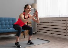 Happy fitness woman doing squat exercise at home. Young happy fitness woman doing squat exercise at home stock image