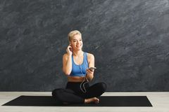Happy fitness woman having rest in gym. Happy fitness woman having rest and listening to music. Young girl sitting on mat in headphones. Bodybuilding, healthy Stock Photography