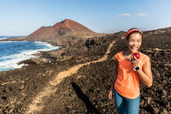 Happy fitness woman on hiking trail eating apple. Happy hiker hiking on mountain trail path taking a break eating a healthy snack - apple fruit. Fitness woman royalty free stock photo