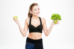Happy fitness woman holding apple and lettuce Stock Photos