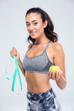 Happy fitness woman holding apple and measuring typ Royalty Free Stock Photography