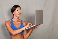 Happy fitness woman holding laptop computer. While looking at camera on grey texture background Stock Photos