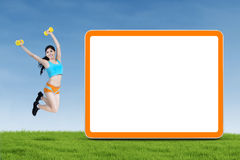 Happy fitness woman jumps next to blank board Stock Image