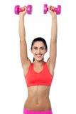 Happy fitness woman lifting dumbbells Stock Photos