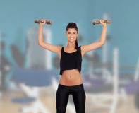 Happy fitness woman lifting dumbbells Royalty Free Stock Images