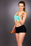 Happy fitness woman lifting dumbbells smiling cheerful, fresh an Stock Images