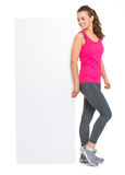 Happy fitness woman looking on blank billboard Royalty Free Stock Images