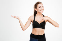 Happy fitness woman pointing finger at copyspace on her palm Stock Photo