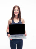 Happy fitness woman showing laptop screen Royalty Free Stock Photos