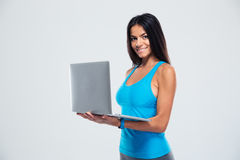 Happy fitness woman using laptop Stock Images