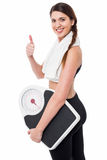 Happy Fitness woman with a weighing scale. Healthy young woman with a weight scale and thumps up Stock Images