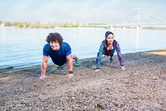 Fitness woman and fitness man doing push-ups outdoors royalty free stock images