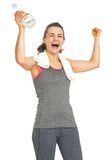 Happy fitness young woman with bottle of water rejoicing success Royalty Free Stock Photos