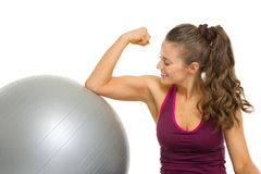 Happy fitness young woman checking biceps Royalty Free Stock Photography