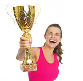 Happy fitness young woman with gold trophy cup rejoicing. Isolated on white stock images