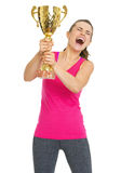 Happy fitness young woman holding gold trophy cup Stock Photos