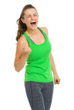 Happy fitness young woman making fist pump gesture. Isolated on white Royalty Free Stock Photo