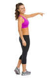 Happy fitness young woman pointing on copy space Royalty Free Stock Image