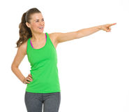 Happy fitness young woman pointing on copy space Stock Photos
