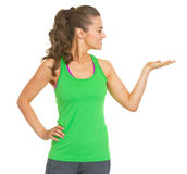 Happy fitness young woman presenting something on empty palm Royalty Free Stock Image