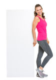 Happy fitness young woman showing blank billboard Royalty Free Stock Photography
