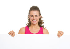 Happy fitness young woman showing blank billboard. Isolated on white Royalty Free Stock Photo