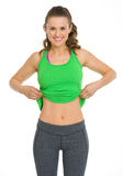 Happy fitness young woman showing flat belly. Isolated on white Royalty Free Stock Photography