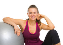 Happy fitness woman sitting with fitness ball Stock Photography