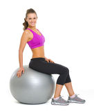 Happy fitness young woman sitting on fitness ball Royalty Free Stock Images